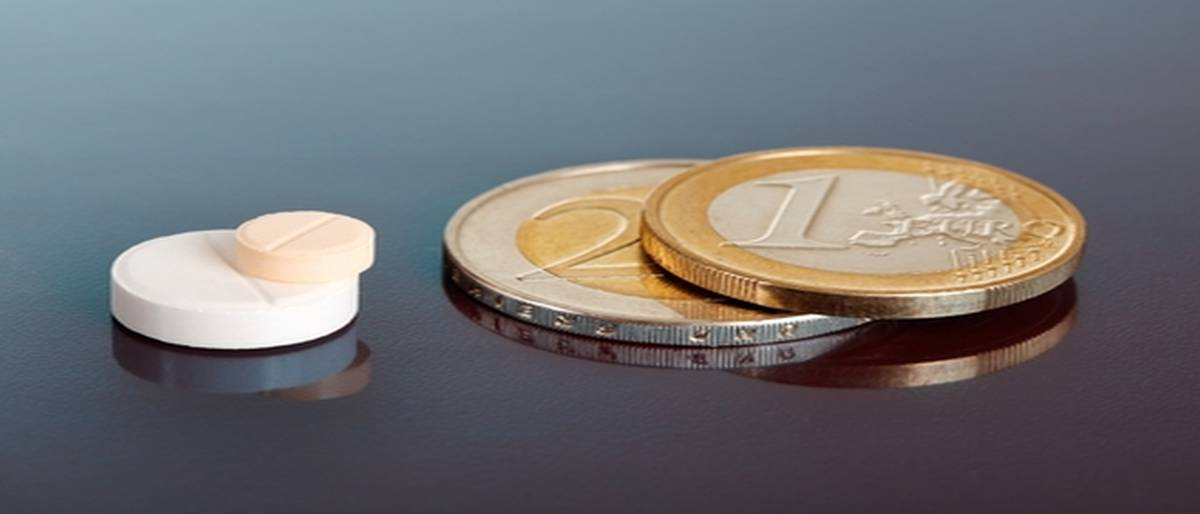 Closeup on pair of stacked pills near pair of similarly arranged euro coins